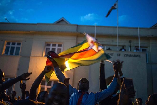 População foi às ruas de Harare, capital do Zimbábue, para comemorar a renúncia de Mugabe   MUJAHID SAFODIEN/AFP