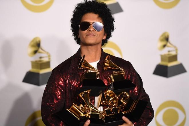 O cantor Bruno Mars com os troféus que ganhou durante a 60ª edição do Grammy | DON EMMERTAFP