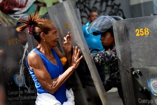 Mulher confronta a polícia durante protesto contra a falta de comida, em Caracas, em 28 de dezembro de 2017. | FEDERICO PARRA/AFP