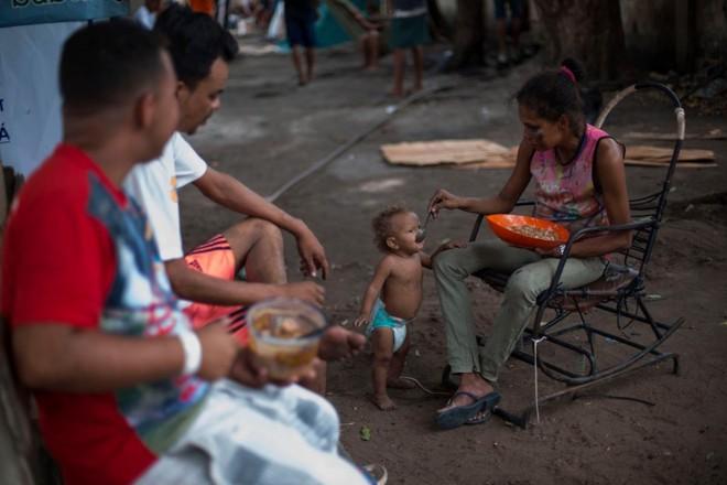 Venezuelanos saem do país para não passar fome: em um abrigo para refugiados em Boa Vista, uma mãe alimenta seu filho | MAURO PIMENTEL AFP