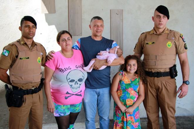 Aurora com os pais e os policiais que a salvaram: à esquerda Wesley Alves Soares, que ajudou no parto,  e à direita Walter Dudek Filho, que a salvou de engasgamento. | Soldado Adilson Voinaski Afonso/Polícia Militar