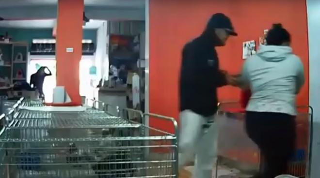 Os dois assaltantes, um deles à frente, rendendo uma funcionária da loja ,e outro ao fundo, na porta do estabelecimento.   Reprodução/Vídeo