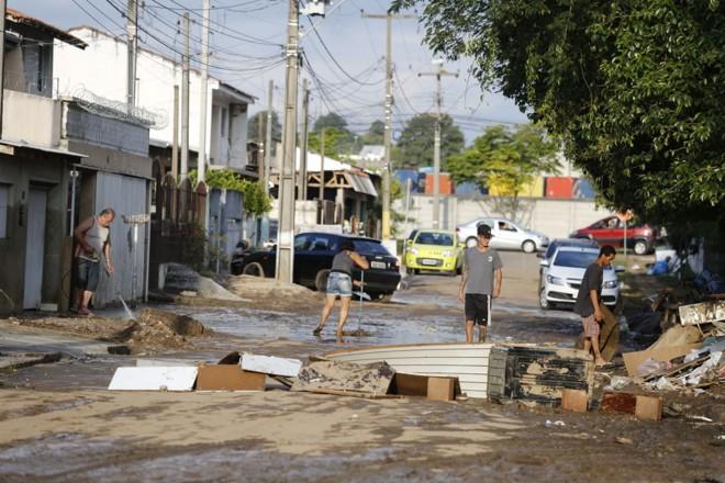 Moradores da CIC limpam as casas após a enchente de sábado. | Marco Charneski/Tribuna do Paraná