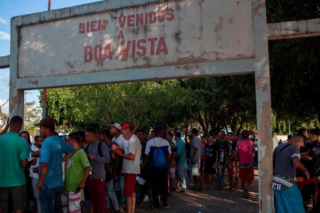 Refugiados venezuelanos esperam em fila para conseguir comida de voluntários na praça Simón Bolívar, em Boa Vista, Roraima, Brasil | MAURO PIMENTEL/ AFP