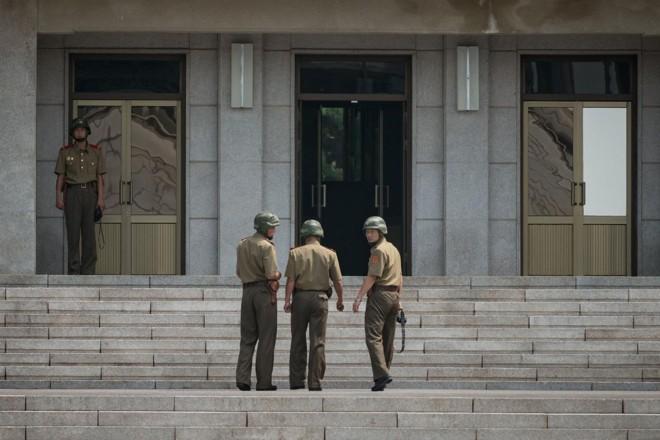 Soldados norte-coreanos caminham em frente ao Pavilhão Panmon, no lado norte da aldeia de Panmunjom,  que separa a Coreia do Norte e a do Sul | ED JONES/ AFP