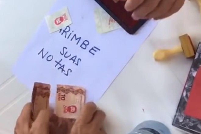 Simpatizantes do ex-presidente Lula carimbam rosto do petista em cédulas de dinheiro.   Reprodução/ YouTube