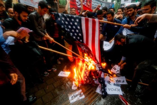 Iranianos queimam bandeiras dos Estados Unidos durante protestos em Teerã | ATTA KENARE/AFP