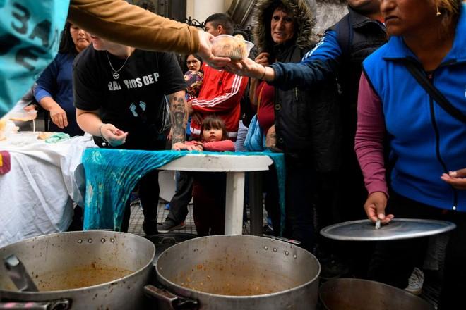 Pessoas recebem sopa, em frente ao Banco Central da Argentina, em Buenos Aires. Peso perdeu 25,5% de seu valor em um ano | EITAN ABRAMOVICH/AFP