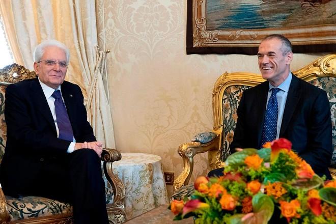 O presidente italiano Sergio Mattarella (E) se encontrou com Carlo Cottarelli (D) no palácio presidencial, em Roma, depois de lhe dar mandato para formar um governo provisório   PAOLO GIANDOTTIAFP