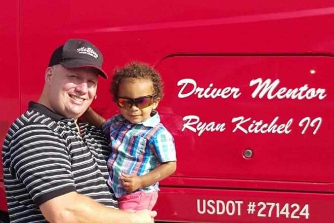 Ryan Kitchel segura seu filho em frente ao seu caminhão. Kitchel se sente feliz por ter conseguido mudar para uma empresa que o leva para casa nos fins de semana e paga bem. | Ryan Kitchel/Arquivo Pessoal