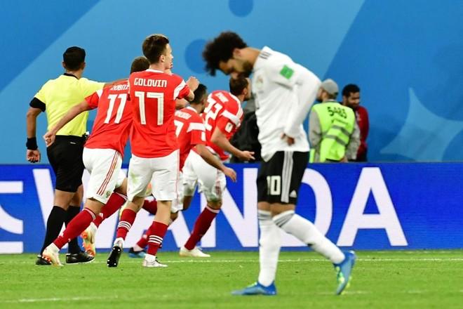 Egípcio Salah lamenta enquanto atletas da Rússia celebram um dos três gols do time da casa | GIUSEPPE CACACE/AFP