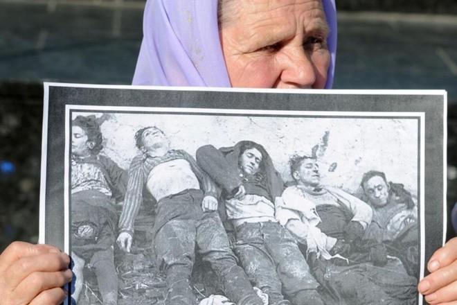Mulher segura retrato com imagens de pessoas mortas durante o regime de Joseph Stalin   AFP PHOTO / YURIY DYACHYSHYN
