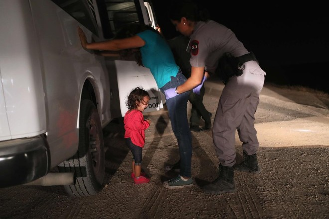 Garotinha hondurenha de 2 anos chora ao ver sua mãe ser revistada e detida pela Patrulha da Fronteira perto da fronteira entre os EUA e o México   JOHN MOORE/AFP