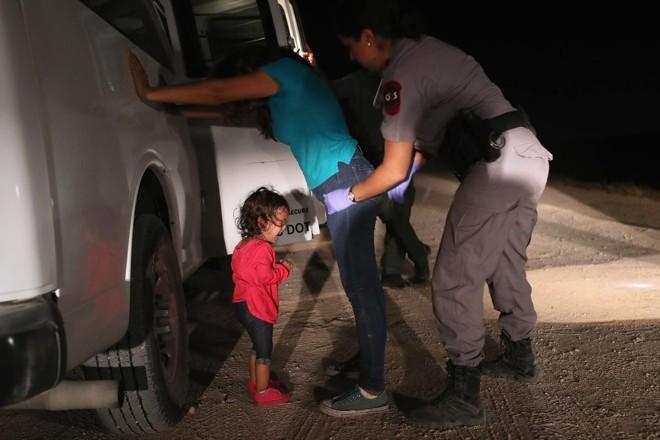 Uma menina hondurenha de dois anos de idade chora enquanto sua mãe é revistada e detida perto da fronteira EUA-México em 12 de junho de 2018 em McAllen, Texas | JOHN MOOREAFP
