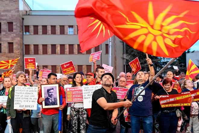 Manifestantes agitam bandeiras em frente ao parlamento em Skopje, capital da Macedônia | ROBERT ATANASOVSKIAFP