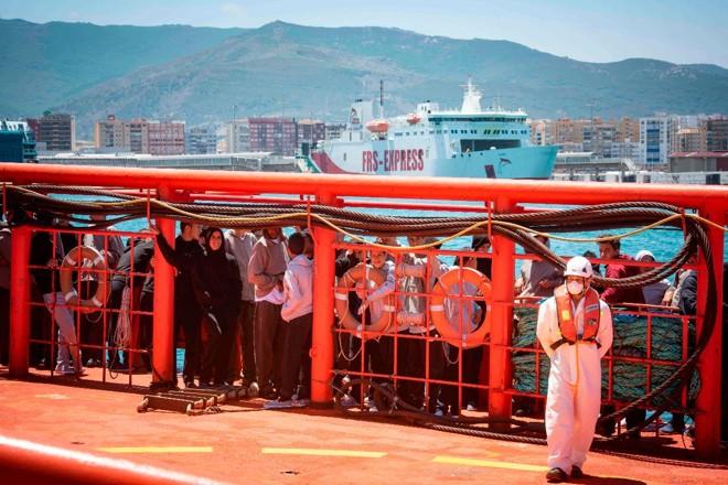 Migrantes aguardam pelo desembarque no porto de Algeciras, na Espanha | MARCOS MORENO/AFP