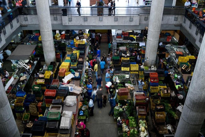 Pessoas fazem compras no mercado municipal de Chacao, em Caracas, em junho de 2018. A pior crise econômica da história da Venezuela causa falta de alimentos, água e medicamentos | FEDERICO PARRAAFP