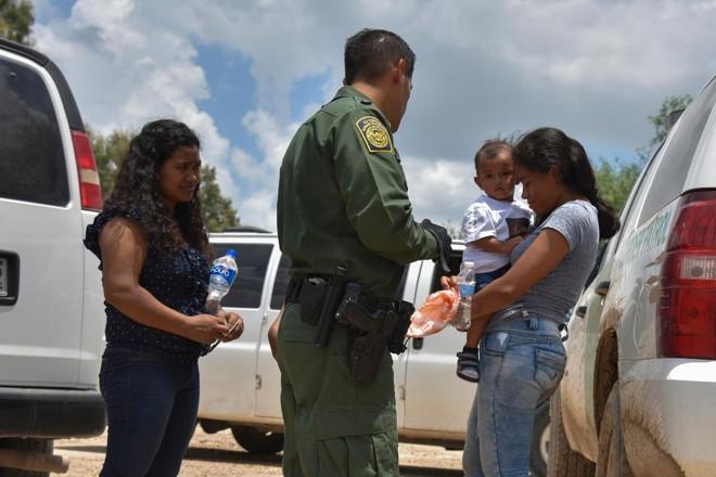 Duas mães de Honduras e seus filhos - uma de 12 anos, que não aparece na imagem, e uma de 1 ano - são detidas por um agente da Patrulha de Fronteira no Texas depois de atravessar o rio Grande | Jahi ChikwendiuThe Washington Post