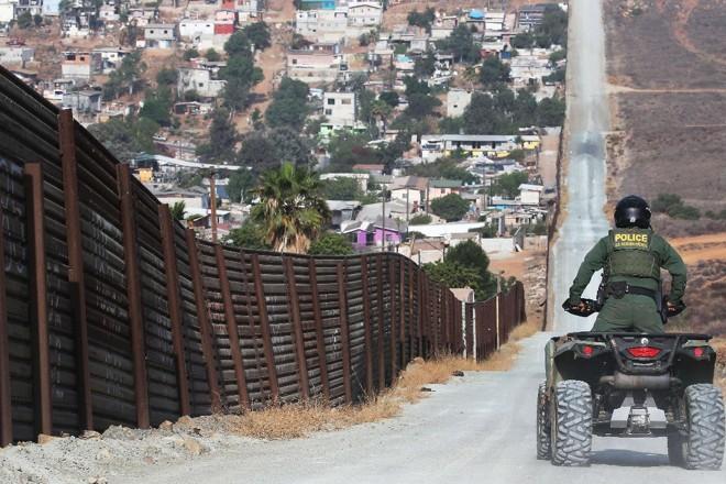 Agente da Patrulha da Fronteira americana monitora a cerca que separa os Estados Unidos do México. em San Diego   MARIO TAMA/AFP
