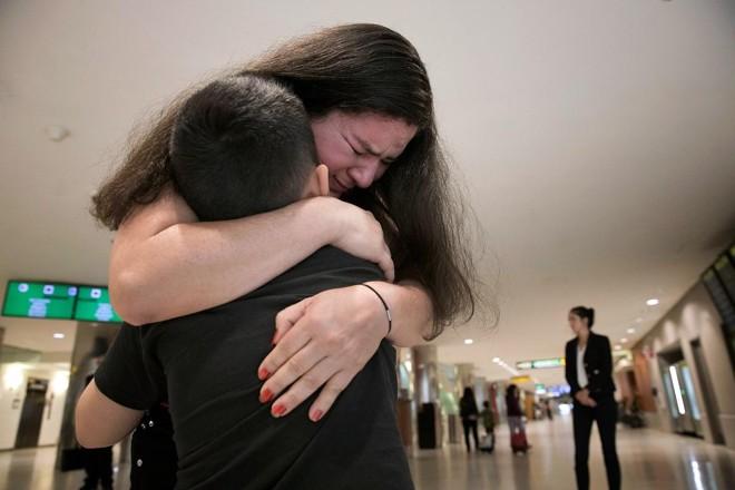 Mãe reencontra filho, no aeroporto de Baltimore-Washington, do qual foi separada ao entrarem nos Estados Unidos | WIN MCNAMEE/AFP