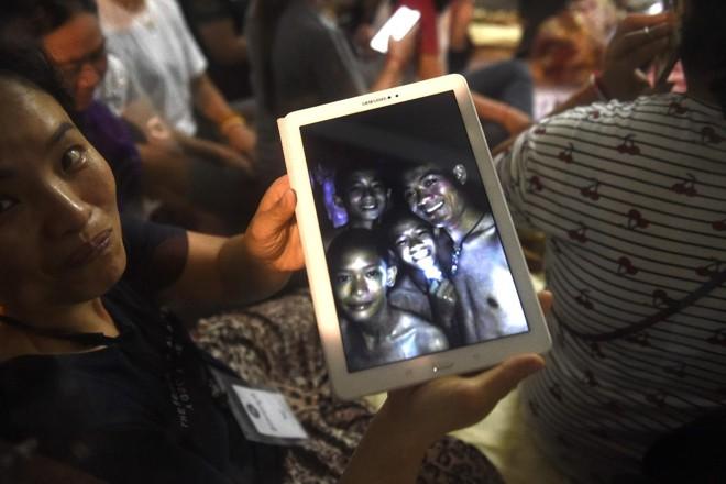 Pais mostram foto de quatro dos 12 meninos que estão presos em uma caverna no Norte da Tailândia   LILLIAN SUWANRUMPHA/AFP