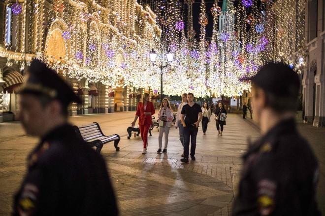 Forças policiais russas montam guarda enquanto torcedores e turistas comemoram na Praça Vermelha de Moscou | ODD ANDERSENAFP