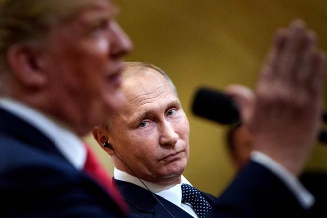 Presidente Vladimir Putin, da Rússia, escuta o presidente americano Donald Trump falar durante coletiva à imprensa, após a cúpula de Helsinque, na Finlândia | BRENDAN SMIALOWSKI/AFP