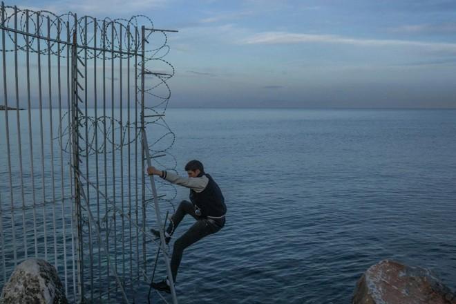 Anas, um imigrante da Argélia, escalando uma cerca ao redor do porto em Mitilene, capital da ilha grega de Lesbos, enquanto tentava entrar escondido em um navio para Atenas, em 4 de março de 2018 | MAURICIO LIMA/NYT