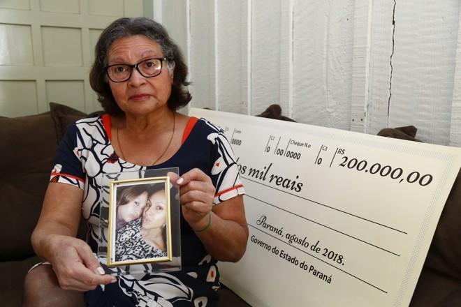Maria Salete, com o retrato da filha Tatiane e da neta Julia, e o cheque que vai mudar a vida da família. | Aniele Nascimento/Gazeta do Povo