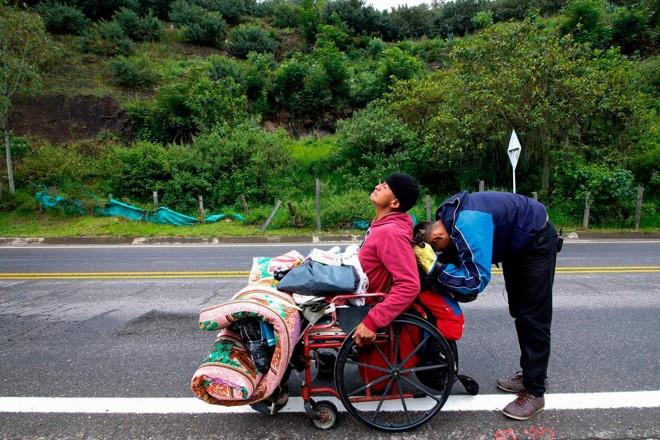 Imigrante venezuelano Jefferson Alexis e seu pai Jose Agustin Lopez, em uma cadeira de rodas, param para descansar enquanto viajam pela estrada que liga Cucuta e Pamplona, na Colômbia   SCHNEYDER MENDOZA/AFP