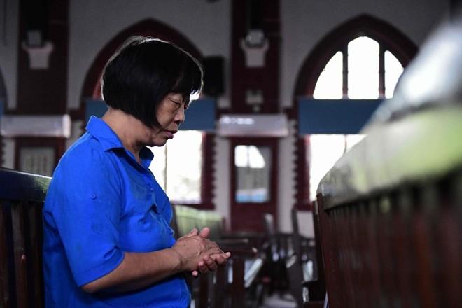 Mulher reza dentro da igreja Christian Glory, em Wuhan, na China. Acordo histórico entre a China e o Vaticano é uma vitória para Pequim | NICOLAS ASFOURI/AFP