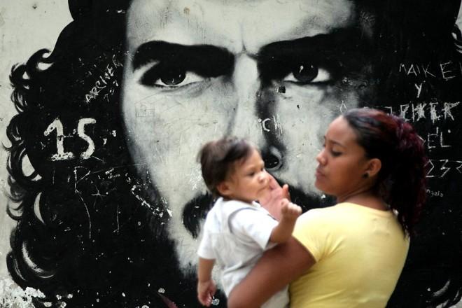 Uma mãe com seu filho passa por um grafitti retratando o revolucionário argentino Ernesto Che Guevara em um bairro de baixa renda de Caracas, em 8 de outubro de 2008. | THOMAS COEX/AFP