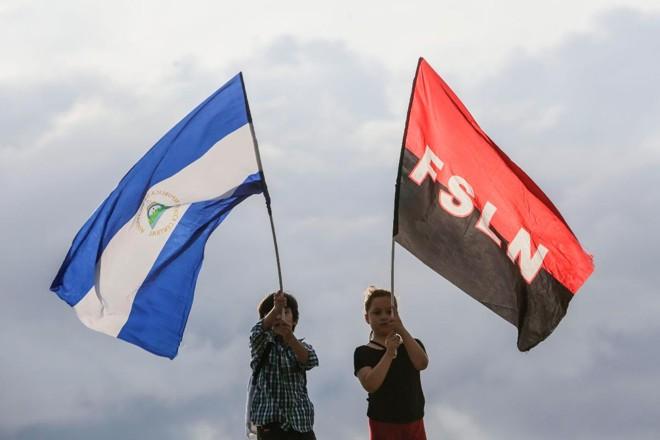 Crianças agitam bandeiras da Nicarágua e do movimento sandinista, durante manifestação de apoio ao ditador Daniel Ortega | INTI OCON/AFP