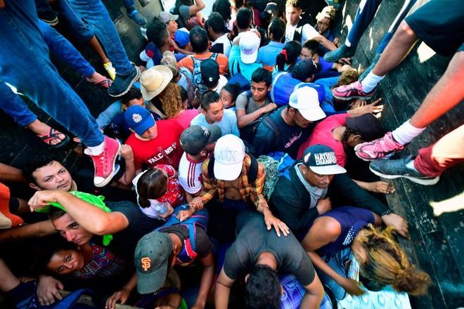 Migrantes hondurenhos a bordo de um caminhão em Metapa, a caminho de Tapachula, no México, em 22 de outubro de 2018. Grupo seguirá para os EUA   PEDRO PARDO/AFP