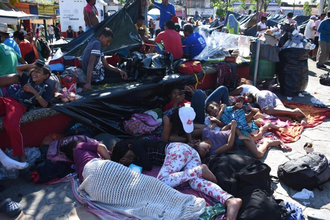 Migrantes hondurenhos que participam de caravana que vai aos EUA descansam durante a jornada | JOHAN ORDONEZ/AFP