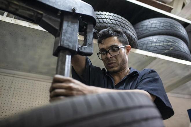 Yhoan Guerrero conserta pneus em sua oficina, dado o alto preço de um pneu novo na Venezuela | Carlos Becerra/Bloomberg