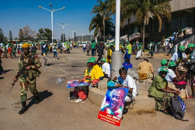 Um soldado passa por partidários de Emmerson Mnangagwa, presidente do Zimbábue, durante uma manifestação do partido no Estádio Nacional em Harare, no Zimbábue, em 28 de julho de 2018 | Waldo Swiegers/Bloomberg