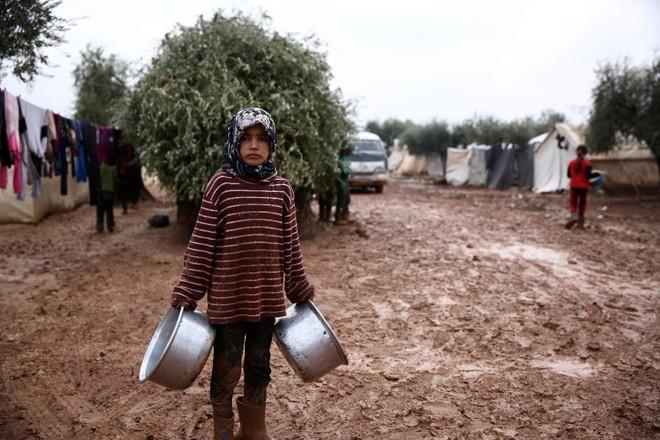 Menina síria em acampamento de desabrigados perto da vila de Shamarin, próximo à fronteira com a Turquia, em 6 de dezembro | NAZEER AL-KHATIB /AFP