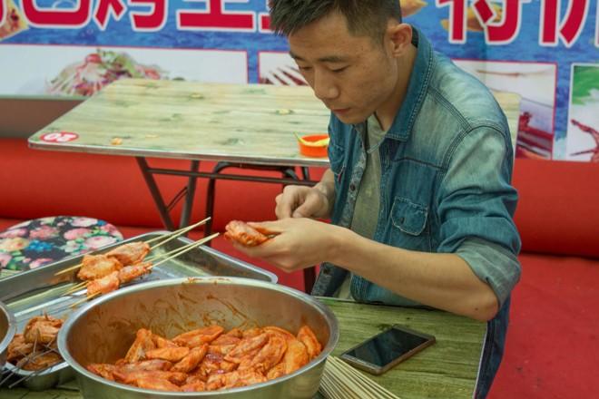 Vendedor  de rua prepara asas de frango ao molho na província chinesa de Suifenhe | BigStock/