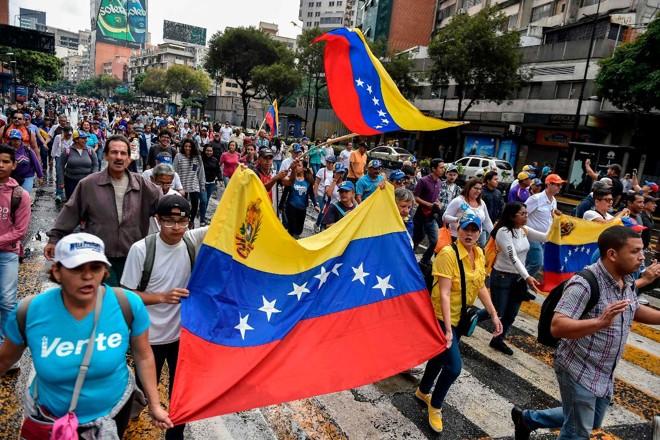 Na ruas de Caracas, milhares de pessoas protestam contra o ditador Nicolás Maduro | LUIS ROBAYO/AFP