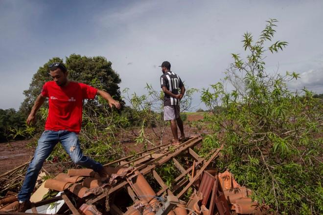 Moradores de Brumadinho observam a destruição causada pelo rompimento da barragem da Vale. | Mauro Pimentel/AFP