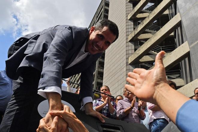 O presidente da Assembleia Nacional da Venezuela, Juan Guaidó, cumprimenta apoiadores durante encontro aberto em Caracas nesta sexta-feira (11)   YURI CORTEZ /AFP