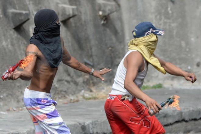 Manifestante jogam coquetéis Molotov durante confrontos com policiais nos arredores de um posto de comando da Guarda Nacional em Cotiza, no norte de Caracas, em 21 de janeiro de 2019   FEDERICO PARRA/AFP