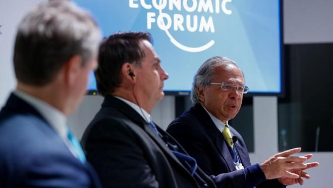 Oministro Paulo Guedes ao lado do presidente Jair Bolsonaro em reunião do Conselho Internacional de Negócios em Davos, na terça (22). Em outro evento, fechado, o ministro da Economia anunciou simplificação de impostos mas também a retomada de taxações.   Alan Santos/PR