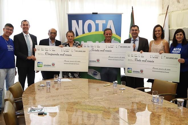 Contemplados no 38º sorteio do Nota Paraná posam com os cheques simbólicos das premiações.   Divulgação/AENPr