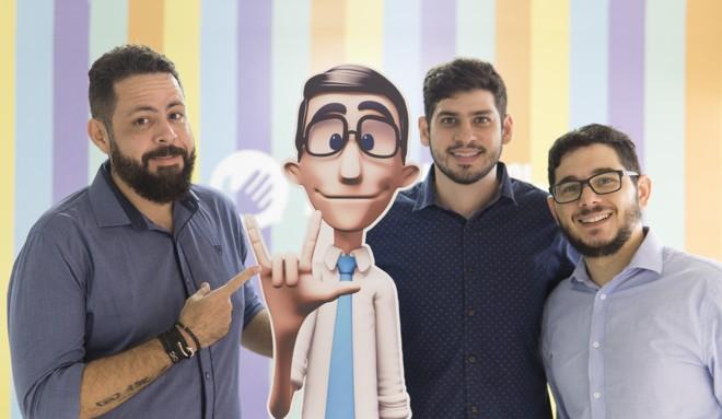 Carlos Wanderlean, Ronaldo Tenório e Thadeu Luz, fundadores da Hand Talk, ao lado da imagem do intérprete virtual da empresa, Hugo. | Divulgação/