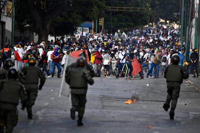 A polícia de choque enfrenta manifestantes durante protesto contra o regime do ditador Nicolás Maduro, 23 de janeiro, em Caracas | YURI CORTEZ /AFP