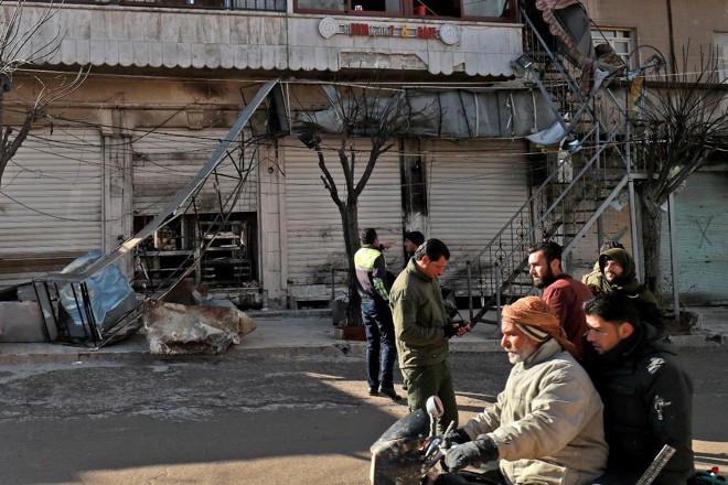Sírios checam o local de um atentado suicida contra as forças de coalizão lideradas pelos EUA na cidade de Manbij, no norte da Síria, que matou quatro militares em 16 de janeiro de 2019   DELIL SOULEIMAN/AFP