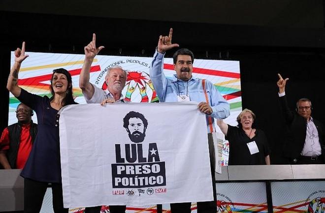 """João Pedro Stédile, líder do MST, e Nicolás Maduro, durante Assembleia Internacional dos Povos. Bandeira traz a expressão """"Lula preso político"""".   Reprodução/Twitter"""
