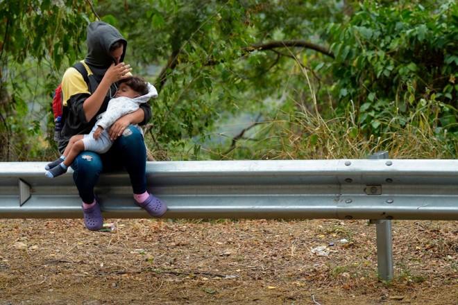 Enquanto segue o impasse sobre a entrada de ajuda humanitária, milhares de venezuelanos deixam diariamente o país. Na foto, uma mulher e uma criança descansam no caminho entre Cúcuta e Pamplona, na Colômbia, em 10 de fevereiro de 2019   RAUL ARBOLEDA/AFP